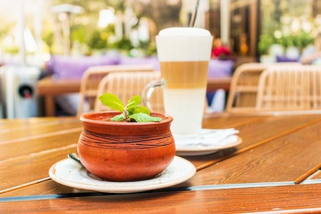 Una tazza di latte caldo e dessert tiramisù con un rametto di menta in una pentola di creta su un tavolo di legno in una caffetteria di strada