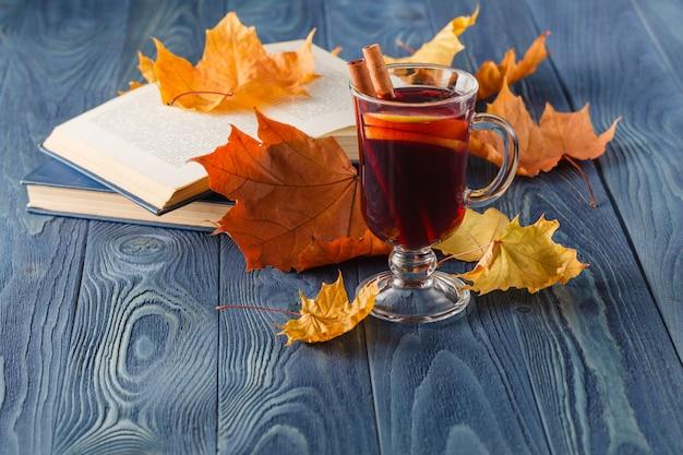 Tazza di vin brulé caldo e foglie di autunno, sulla tavola di legno