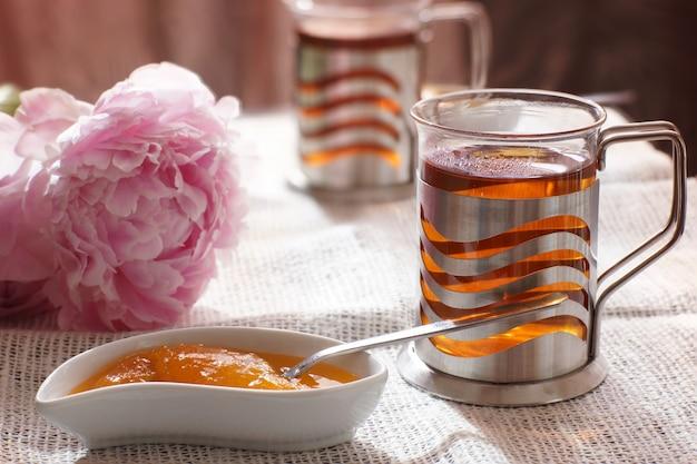 Una tazza di tè caldo accanto a un piattino con dessert e fiori di peonia, colazione per due