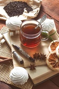 Una tazza di tè caldo, spezie, dolci, busta con penna su un tavolo di legno