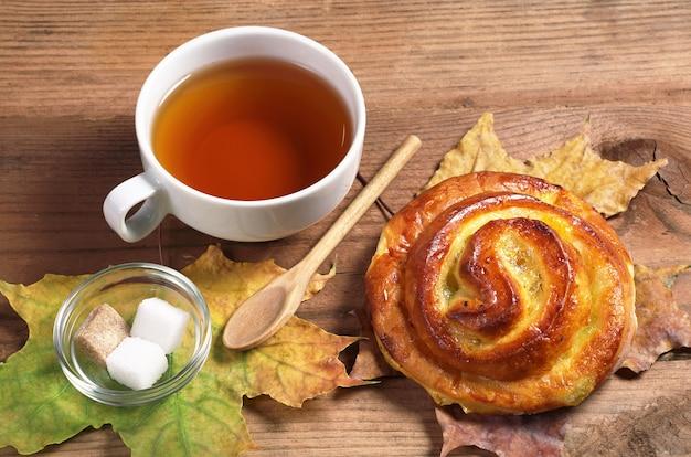 Tazza di tè caldo e panino dolce con marmellata su un vecchio tavolo di legno
