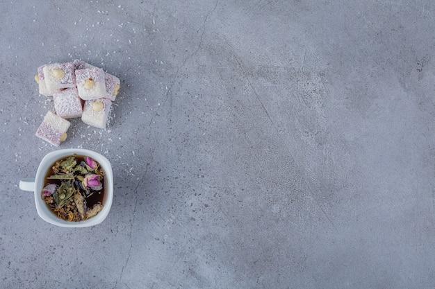Tazza di tè caldo e dolci delizie con noci su pietra.