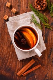 Tazza di tè caldo con arancia e spezie su uno sfondo marrone rustico. avvicinamento