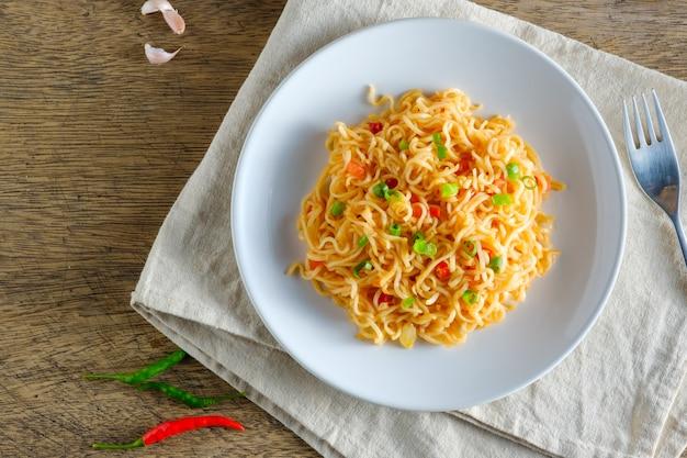 Una tazza di noodles istantanei posizionati su una napery con peperoncino come tagliatelle e copia spazio