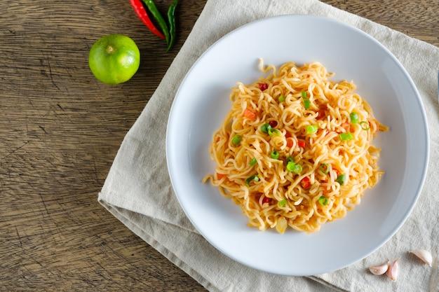 Una tazza di noodles istantanei posizionati su una napery con peperoncino come ingredienti, noodle vista dall'alto e copia spazio