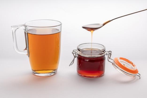 Una tazza di tè tonificante con un cucchiaio di miele, una tazza di vetro con bevanda e un barattolo di miele, miele dorato che fuoriesce dal cucchiaio