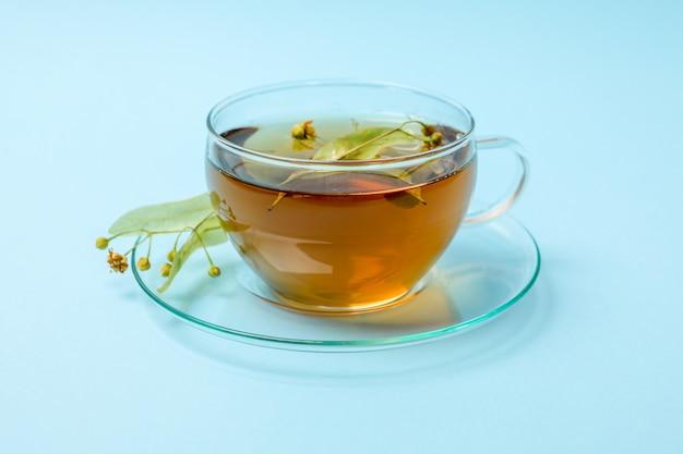 Tazza di tè di tiglio su blu, da vicino