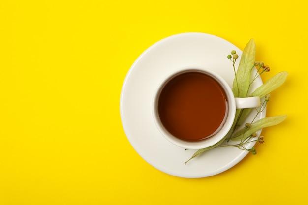 Tazza di tè di tiglio sulla vista gialla e superiore