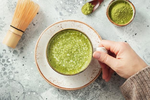 Tazza di tè verde matcha nelle mani della donna. vista dall'alto. posa piatta.