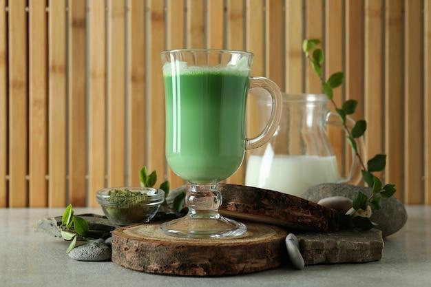 Tazza di latte matcha e accessori per fare su sfondo di bambù