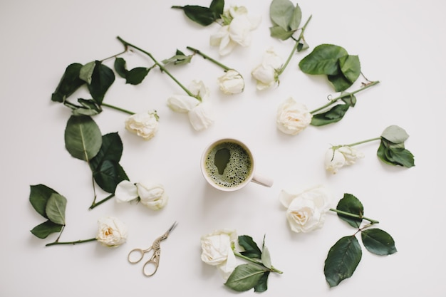 Una tazza di tè matcha e rose su sfondo bianco flatlay vista dall'alto