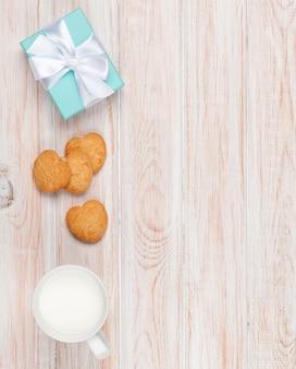 Tazza di latte, biscotti a forma di cuore e confezione regalo su tavolo di legno bianco con spazio per le copie