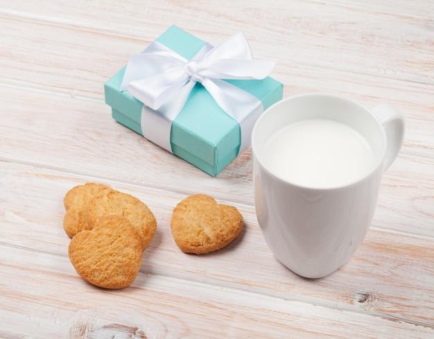 Tazza di latte, biscotti a forma di cuore e confezione regalo su un tavolo di legno bianco