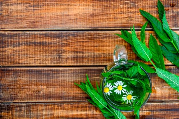 Una tazza di tè alla menta con camomilla su uno sfondo di legno. tisana con camomilla e foglie di menta fresca sul tavolo. copia spazio. telaio. vista dall'alto.