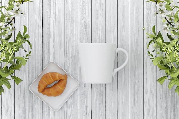 Modello di tazza su fondo di legno con croissant