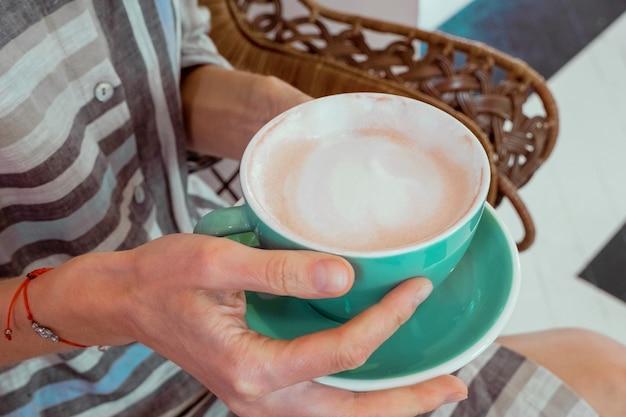 Tazza di caffè mattutino nelle mani di una giovane donna.