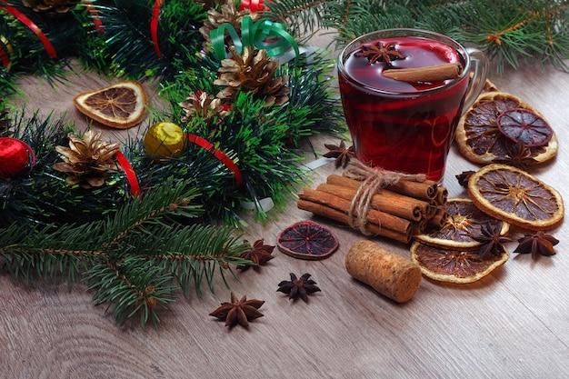 Tazza di vin brulè, spezie e agrumi secchi su un tavolo di legno.