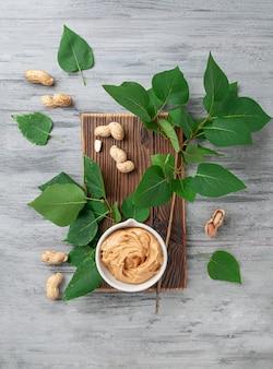 Una tazza di burro di arachidi su una tavola di legno con texture. decorato con verdure e arachidi