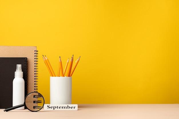 Tazza di matite e taccuini sulla scrivania su sfondo giallo, vista frontale