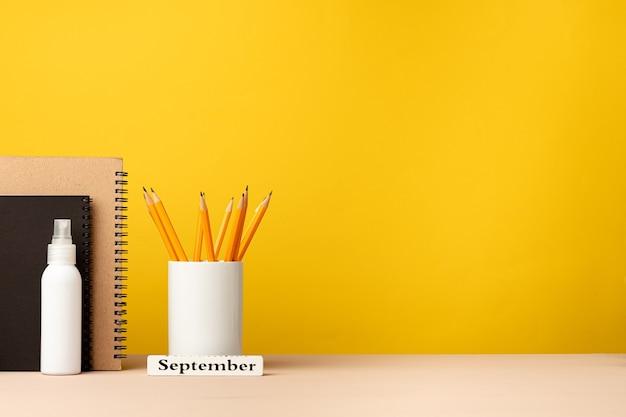 Tazza di matite e taccuini sulla scrivania su sfondo giallo