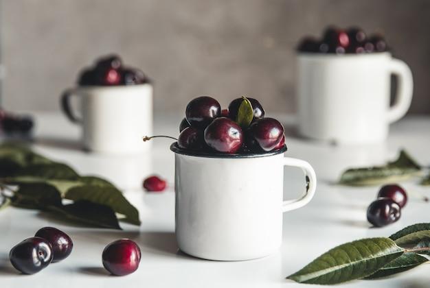 Una tazza di ciliegie dolci su uno sfondo concreto. prodotto ecologico biologico, fattoria. no ogm