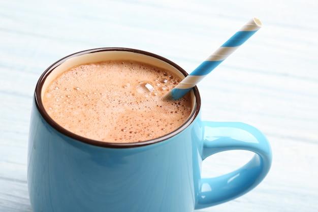 Tazza di gustosa bevanda al cacao su un tavolo di legno leggero, primo piano