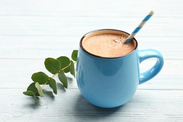 Tazza di gustosa bevanda al cacao su un tavolo di legno chiaro