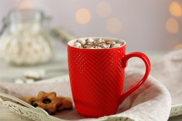 Una tazza di gustoso cacao e marshmallow su sfondo sfocato
