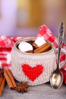 Tazza di gustosa cioccolata calda, su tavola di legno, su sfondo chiaro