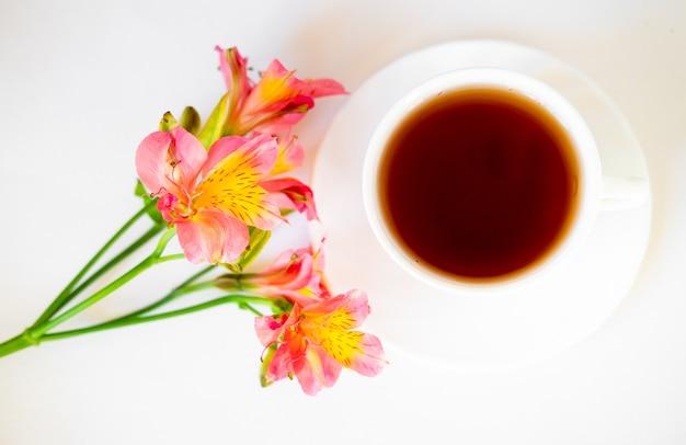 Tazza di tè e alstroemeria su sfondo bianco. fiori copiano il testo. bel mazzo.