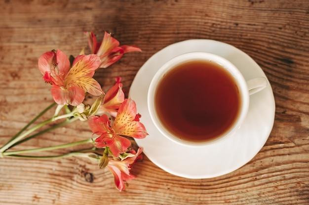 Tazza di tè e alstroemeria sullo sfondo di legno. fiori su uno sfondo marrone. copia testo. bel mazzo.