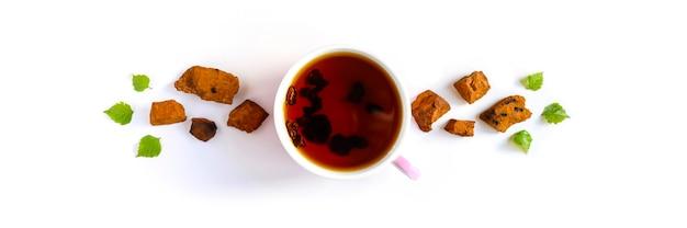 Tazza di tè di betulla chaga funghi e pezzi di funghi chaga schiacciati per la preparazione del tè isolato su uno sfondo bianco.