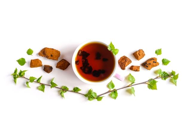 Tazza di tè di betulla chaga fungo e pezzi di fungo chaga schiacciati per la preparazione del tè isolato su una superficie bianca