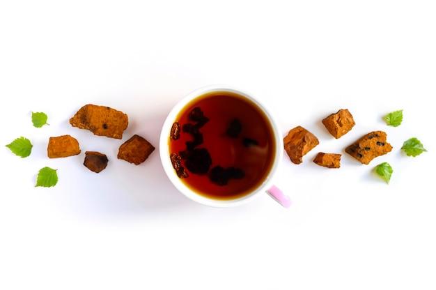 Tazza di tè di betulla chaga funghi e pezzi di funghi chaga schiacciati per la preparazione del tè isolato su un bianco