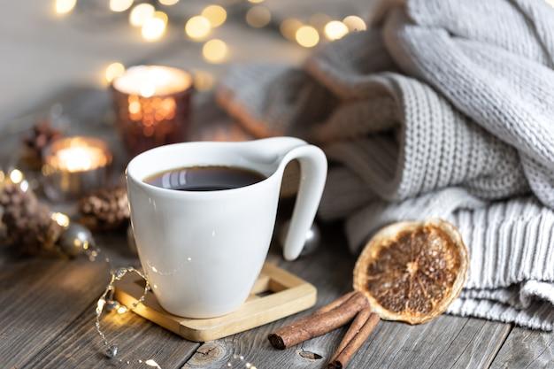 Tazza di tè su uno sfondo sfocato con candele maglioni lavorati a maglia e bokeh