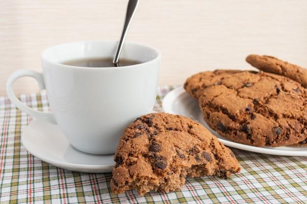 Tazza di tè e biscotti al cioccolato per colazione.