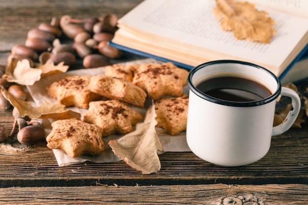 Tazza di tè o caffè con foglie di autunno e biscotti. stagionale, ora del tè, concetto di natura morta.