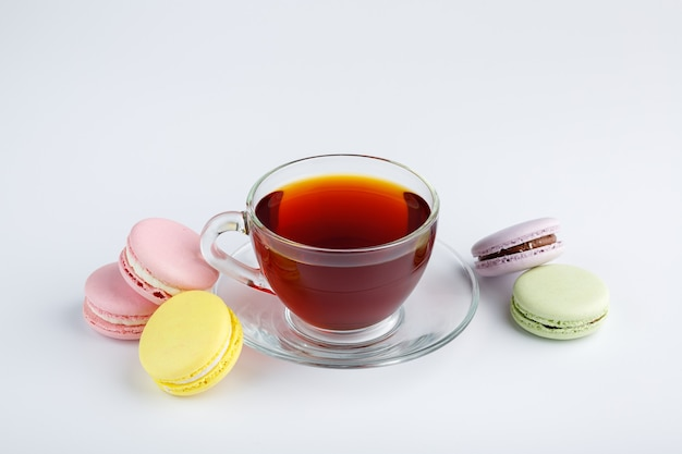 Tazza di tè e amaretti colorati su sfondo bianco