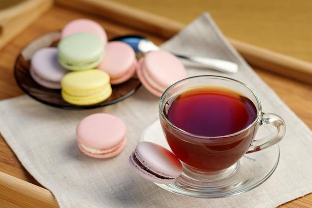 Tazza di tè e amaretti colorati su un vassoio in legno