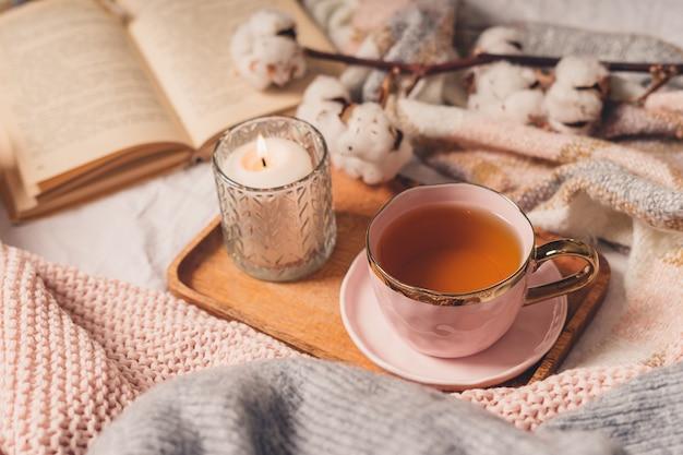 Tazza di tè, cotone, accogliente, libro, candela. accogliente concetto autunno inverno.