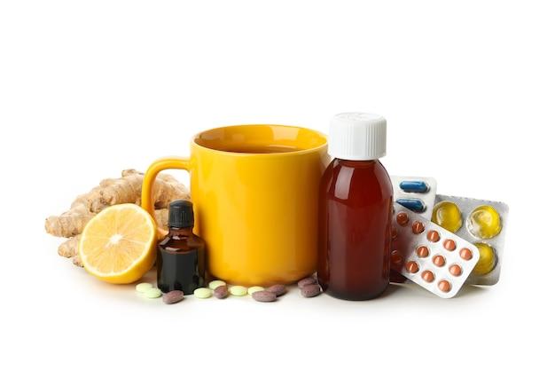 Tazza di tè e medicinali diversi isolati su bianco