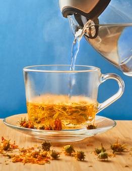 Una tazza di tè con fiori di calendula essiccati, benefici e rischi, metodi di cottura.