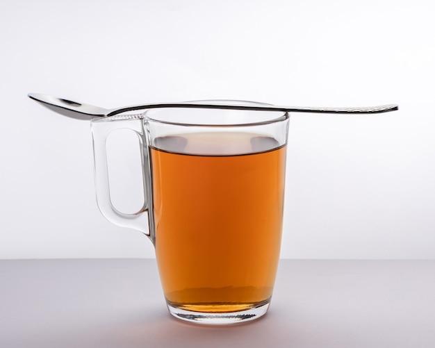 Una tazza di tè in un utensile di vetro con un cucchiaio di metallo sulla tazza