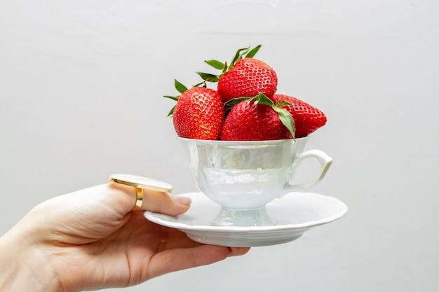 La tazza per il tè è piena di fragole nella mano della ragazza.