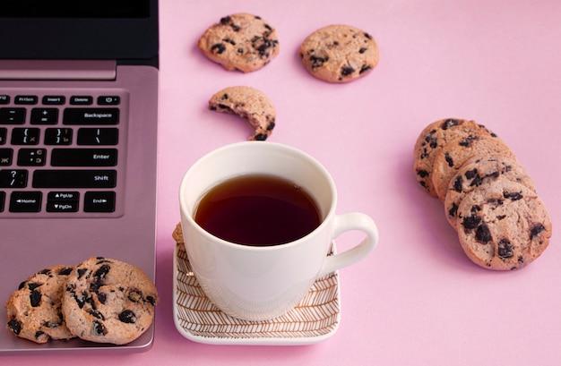 Una tazza di tè è su un piattino vicino a un laptop. biscotti al cioccolato su uno sfondo rosa.