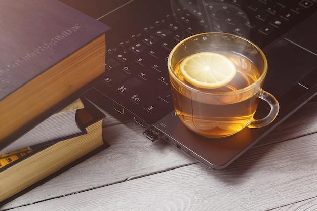 Tazza di tè sul computer portatile e sul libro. concetto di tempo rilassante