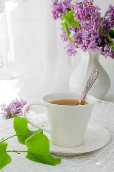 Tazza di tè su un tavolo luminoso vicino a una finestra al mattino e mazzi di fiori con uno spazio di copia