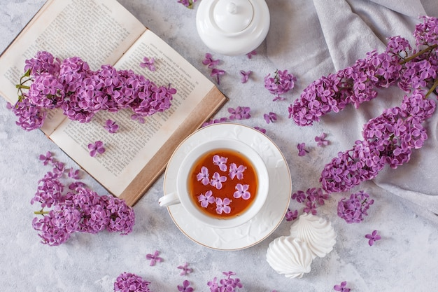 Una tazza di tè, meringa, rami di lillà in fiore e un vecchio libro