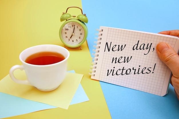 Tazza di tè e un taccuino con la scritta nuovo giorno nuove vittorie