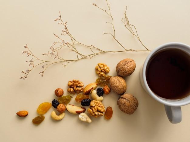 Una tazza di tè, noci e uvetta accanto a fiori secchi su un giallo.